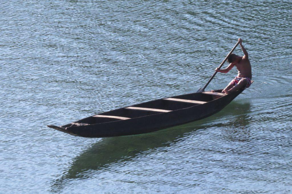 A fisherman diligently rowing his boat